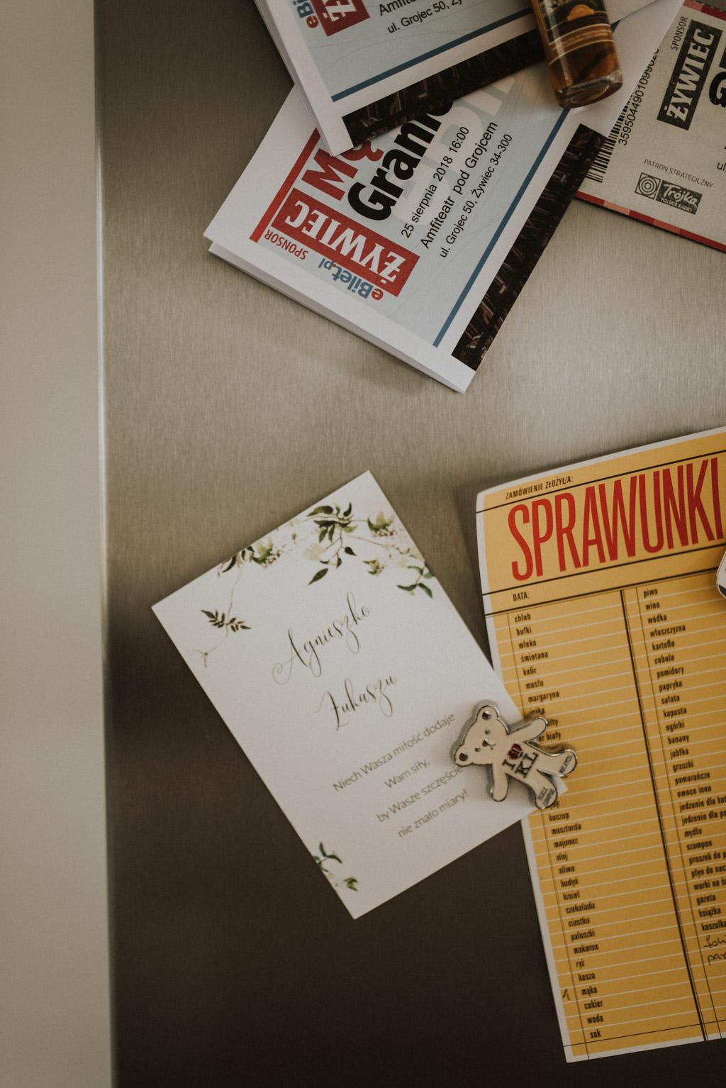 Zaproszenia ślubne przypięte na lodówce