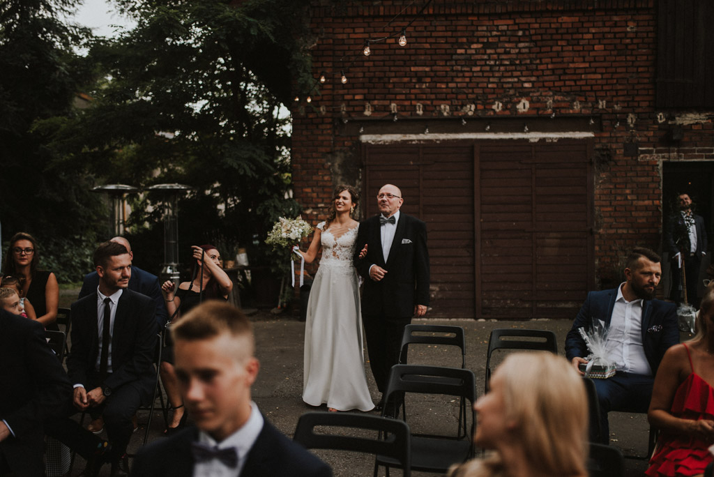Ojciec prowadzi Pannę młodą do ołtarza na ślubie plenerowym w kotulińskiego 6